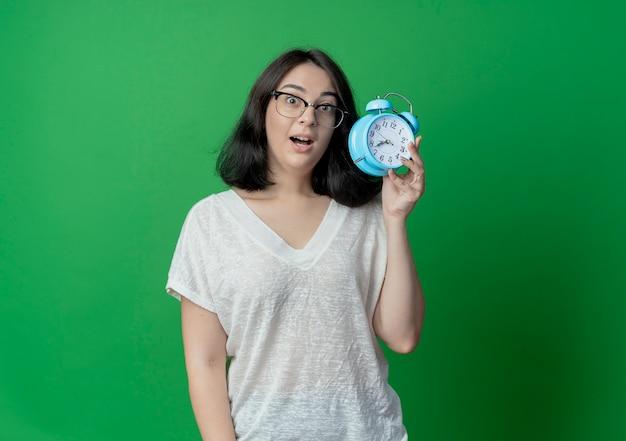 Mulher jovem e bonita impressionada de óculos segurando um despertador