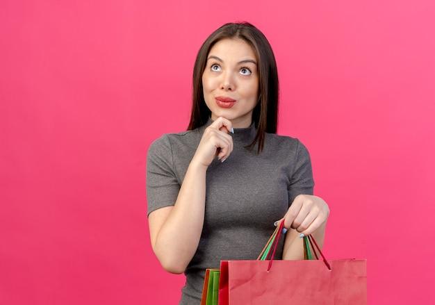 Mulher jovem e bonita impressionada segurando sacolas de compras, olhando para cima e tocando o queixo isolado em um fundo rosa com espaço de cópia