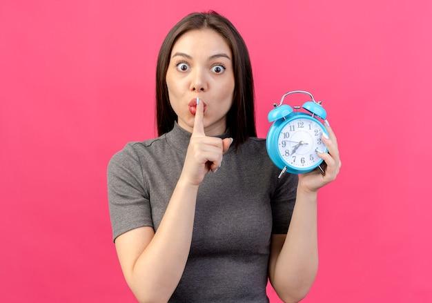 Mulher jovem e bonita impressionada segurando um despertador e gesticulando para o silêncio isolado em um fundo rosa com espaço de cópia