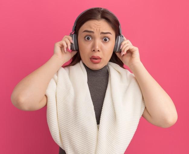 Mulher jovem e bonita impressionada usando e agarrando fones de ouvido
