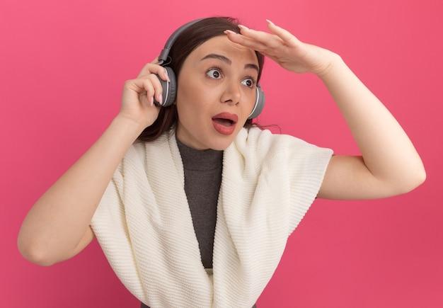 Mulher jovem e bonita impressionada usando e segurando fones de ouvido, mantendo a mão perto da testa e olhando para o lado à distância