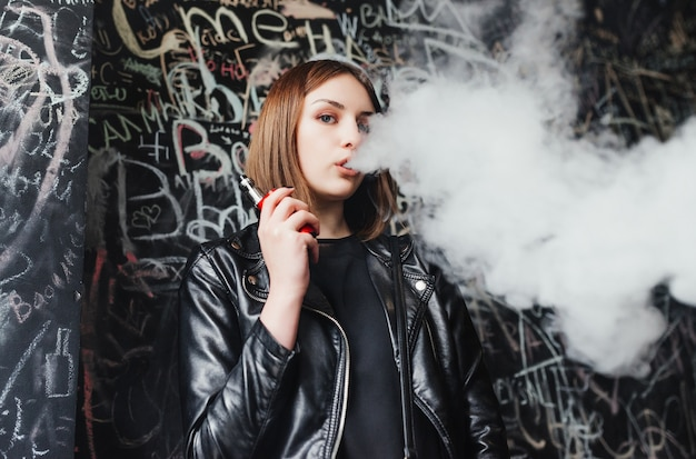 Mulher jovem e bonita inalando fumaça. menina jovem vaping