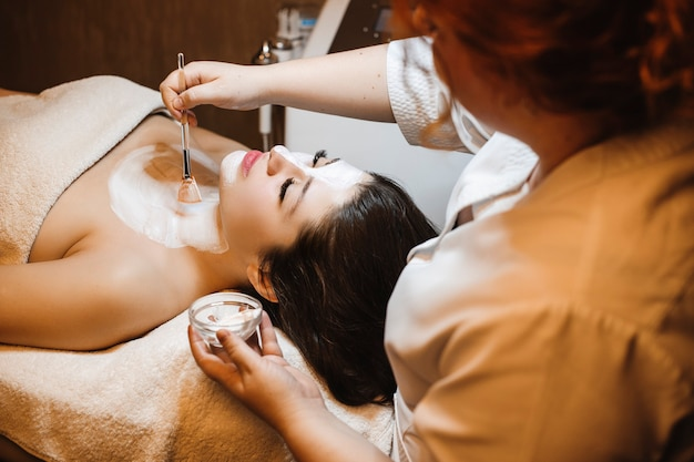 Mulher jovem e bonita inclinada com os olhos fechados em uma cama de spa, tendo uma máscara de hidratação por uma cosmetologista feminina.