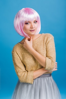 Mulher jovem e bonita incrível com cabelo rosa cortado. suéter dourado, saia de tule cinza, maquiagem de festa, emoções verdadeiras, festa de comemoração, aniversário.
