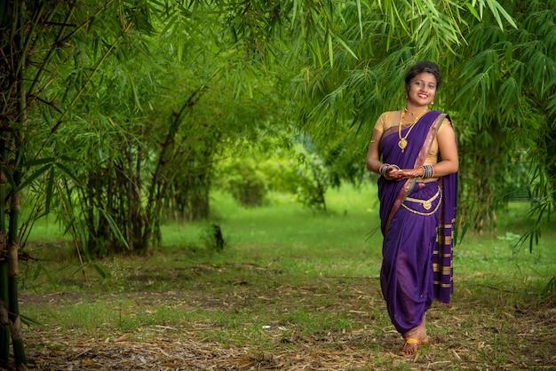 Mulher jovem e bonita indiana em saree tradicional posando ao ar livre