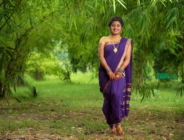 Mulher jovem e bonita indiana no tradicional saree posando ao ar livre