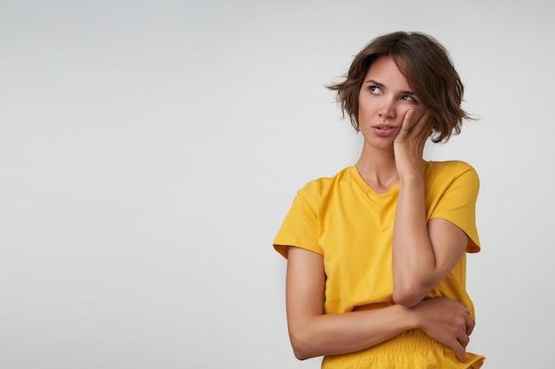 Mulher jovem e bonita intrigada com cabelo castanho curto, segurando a bochecha na mão levantada e olhando para o lado, usando uma camiseta amarela enquanto posava
