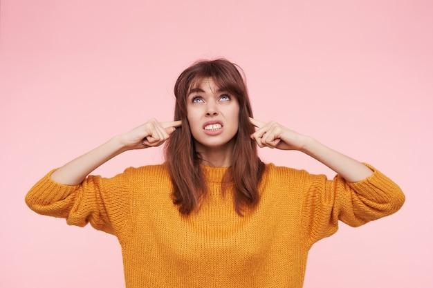 Mulher jovem e bonita irritada com os dedos indicadores nas orelhas enquanto tenta evitar sons altos, franzindo a testa enquanto olha para cima, isolada sobre a parede rosa