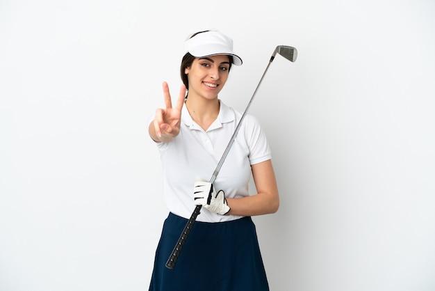 Mulher jovem e bonita jogador de golfe isolada no fundo branco sorrindo e mostrando sinal de vitória