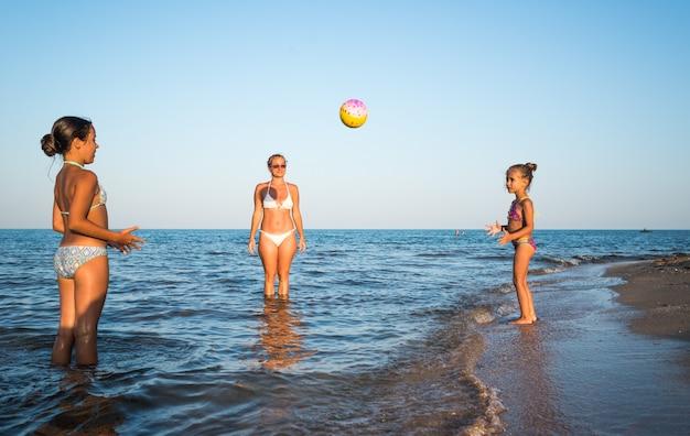 Mulher jovem e bonita jogando bola com suas filhas encantadoras na beira-mar