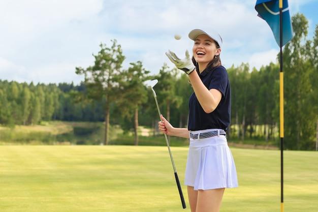 Mulher jovem e bonita jogando uma bola de golfe e sorrindo enquanto está de pé no campo de golfe