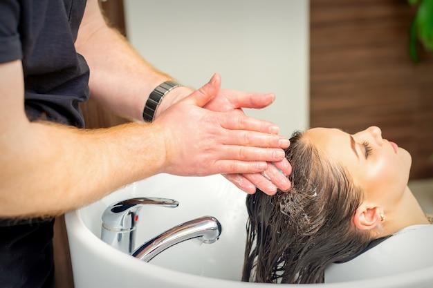 Mulher jovem e bonita lavando o cabelo com as mãos do cabeleireiro masculino em salão de cabeleireiro