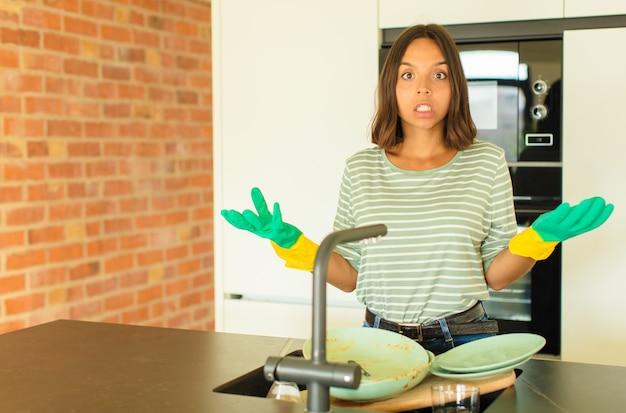 Mulher jovem e bonita lavando pratos boquiaberta e pasma, chocada e atônita com uma surpresa inacreditável