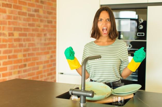 Mulher jovem e bonita lavando pratos, gritando agressivamente com uma expressão de raiva ou com os punhos cerrados celebrando o sucesso