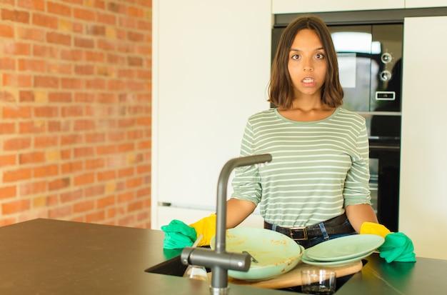 Mulher jovem e bonita lavando pratos parecendo muito chocada ou surpresa, olhando com a boca aberta dizendo uau