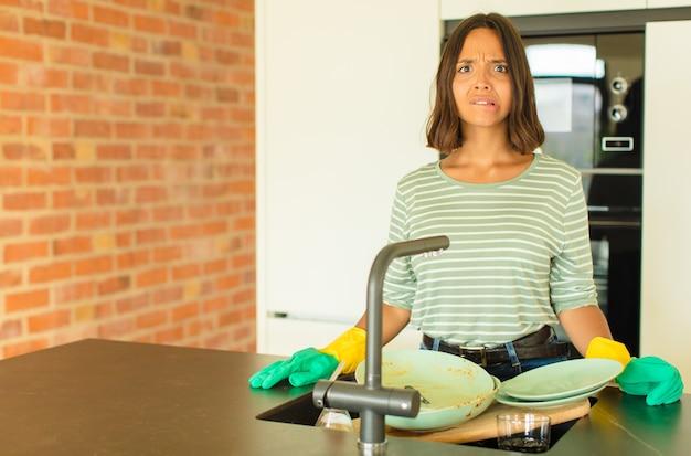 Mulher jovem e bonita lavando pratos parecendo perplexa e confusa, mordendo o lábio com um gesto nervoso, sem saber a resposta para o problema