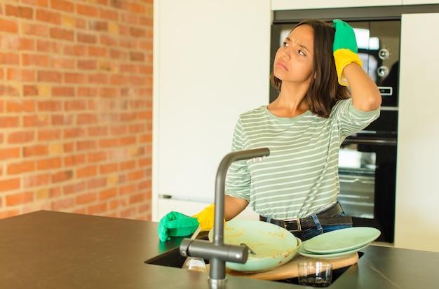 Mulher jovem e bonita lavando pratos, sentindo-se perplexa e confusa, coçando a cabeça e olhando para o lado