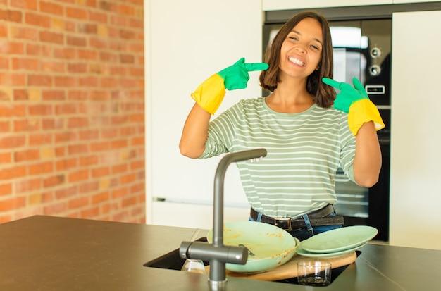Mulher jovem e bonita lavando pratos sorrindo com confiança apontando para o próprio sorriso largo, atitude positiva, relaxada e satisfeita
