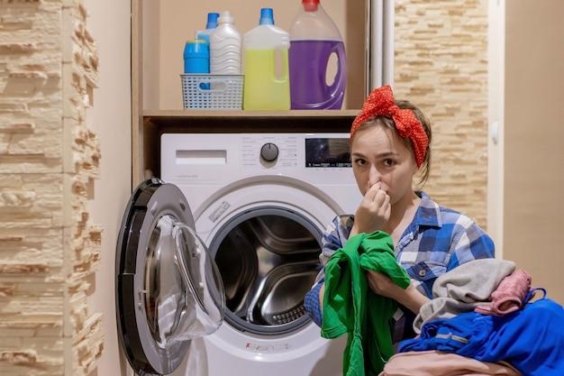 Mulher jovem e bonita lavando roupa. tarefas domésticas