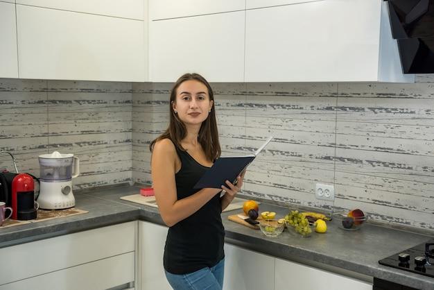 Mulher jovem e bonita lê um caderno na cozinha para cozinhar alimentos saudáveis para o café da manhã.