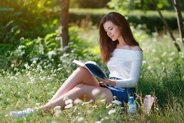 Mulher jovem e bonita lê um livro em um parque de verão ao ar livre.
