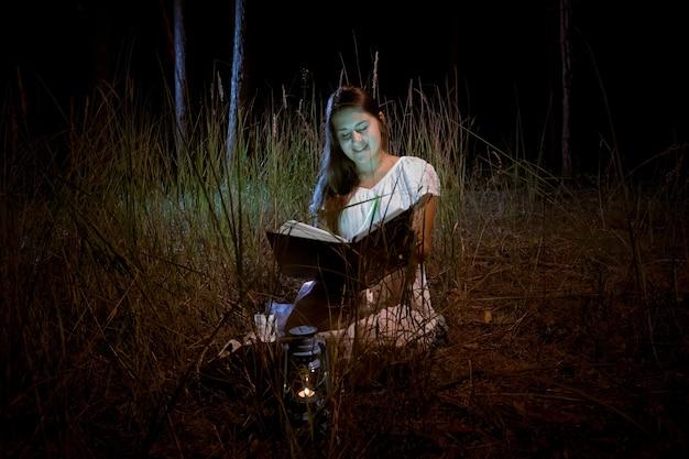 Mulher jovem e bonita lendo livro de mágica na floresta à noite escura