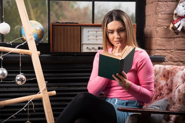 Mulher jovem e bonita lendo livro em casa