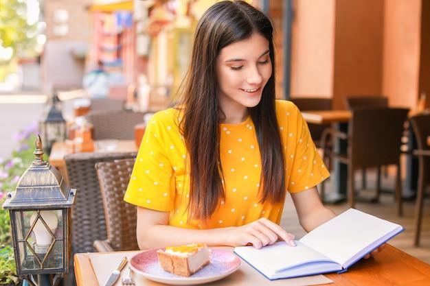 Mulher jovem e bonita lendo livro em um café de rua