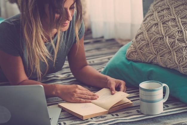 Mulher jovem e bonita lendo livro enquanto estava deitado no tapete ao lado do laptop e do vidro em casa. mulher passando seu tempo de lazer deitada no tapete e lendo um livro em casa
