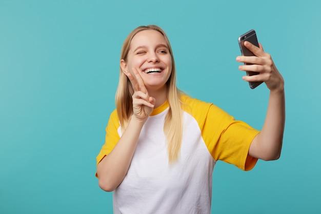 Mulher jovem e bonita loira alegre com cabelo comprido levantando a mão com gesto victore enquanto faz selfie em seu smartphone, em pé contra o azul