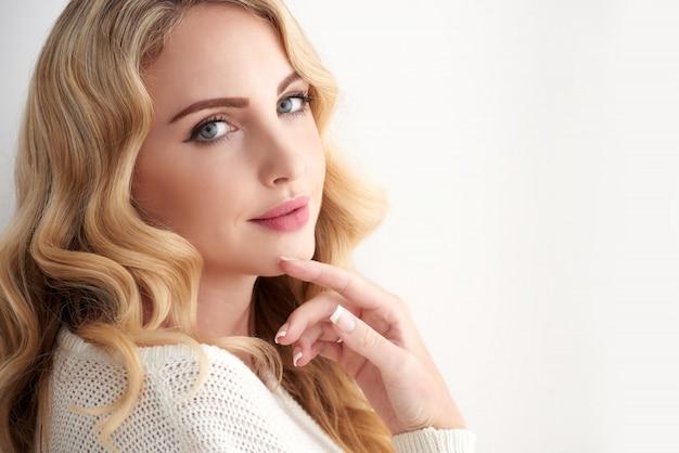 Mulher jovem e bonita loira caucasiana com cabelos ondulados, olhando por cima do ombro