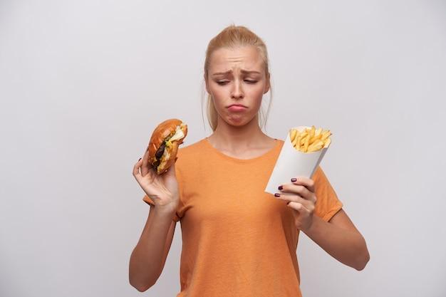 Mulher jovem e bonita loira chateada com uma camiseta laranja, segurando alimentos pouco saudáveis em suas mãos e olhando tristemente para eles, franzindo as sobrancelhas e torcendo a boca enquanto posava sobre um fundo branco