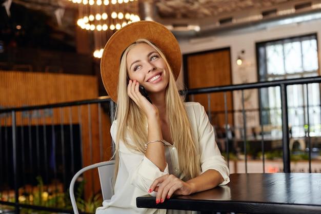 Mulher jovem e bonita loira com cabelo comprido posando sobre o interior do café enquanto fala ao telefone, olhando para o lado alegremente e esperando seu pedido