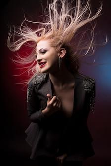 Mulher jovem e bonita loira com cabelo em movimento no estúdio