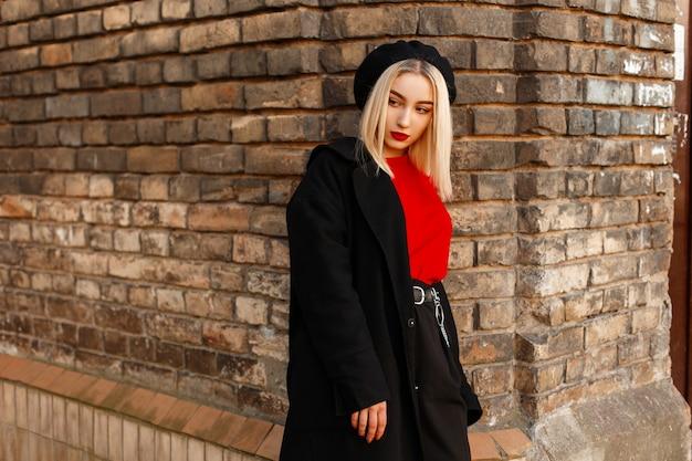 Mulher jovem e bonita loira com lábios vermelhos sensuais em roupas retrô elegantes e uma boina elegante está descansando perto de uma parede de tijolos vintage