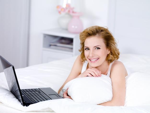 Mulher jovem e bonita loira com um sorriso deitada em uma cama com um laptop