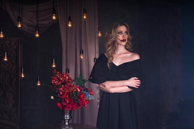 Mulher jovem e bonita loira com um vestido preto com maquiagem de halloween e arte no rosto sangrento, interior vintage