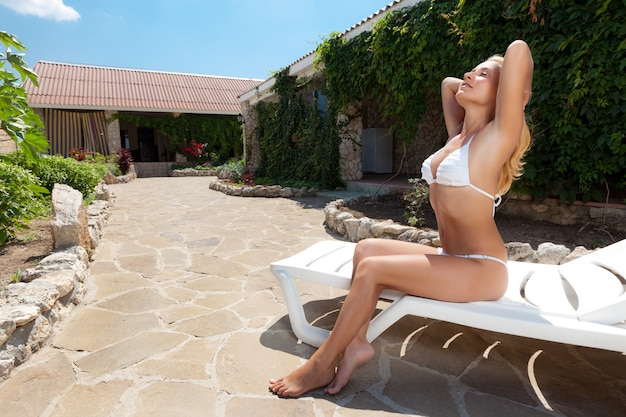 Mulher jovem e bonita loira de biquíni branco com os olhos fechados, deitado numa espreguiçadeira na área da casa de campo e aproveitando o descanso num dia de verão. férias no campo e conceito de descanso