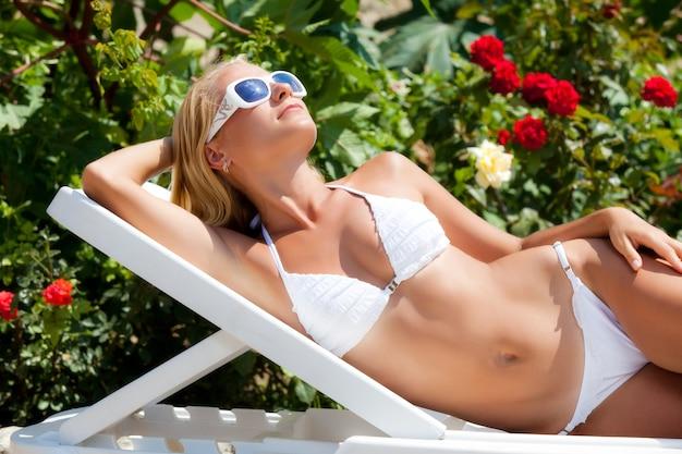 Mulher jovem e bonita loira de biquíni branco e óculos escuros, deitada na espreguiçadeira na área da casa de campo e aproveitando o sol num dia de verão. férias no campo e conceito de descanso
