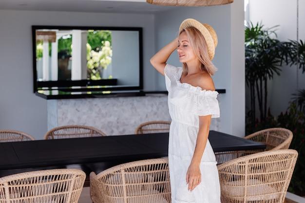 Mulher jovem e bonita loira de cabelo branco na cozinha ao ar livre de uma villa