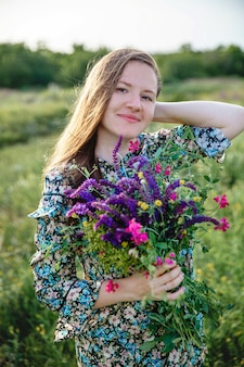 Mulher jovem e bonita loira de cabelos compridos de aparência europeia com um buquê florescendo de flor selvagem.