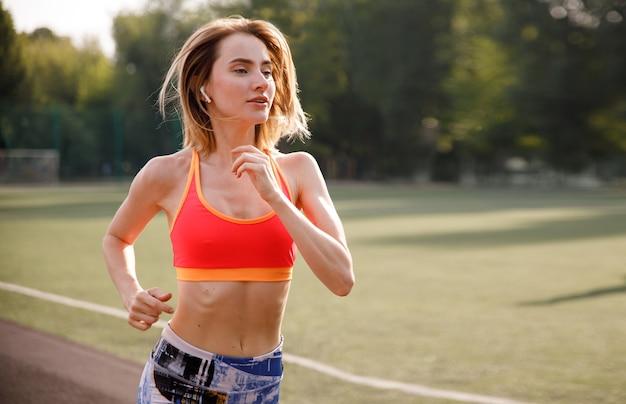 Mulher jovem e bonita loira desportiva correr ao ar livre.