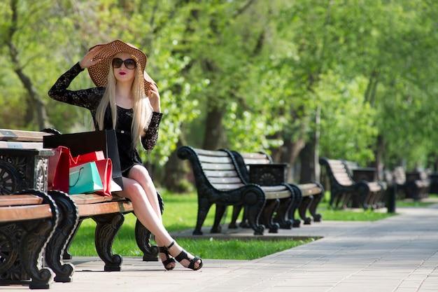 Mulher jovem e bonita loira elegante em um vestido preto, óculos escuros e chapéu com sacolas de compras, sentado em um banco do parque