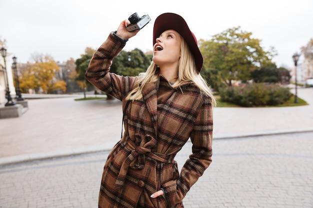 Mulher jovem e bonita loira elegante vestindo um casaco caminhando ao ar livre, tirando fotos com a câmera fotográfica