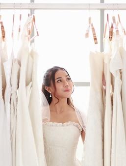 Mulher jovem e bonita loira em pé escolhendo um vestido de noiva. mulher asiática sorridente segurando a mão do vestido de noiva da noiva no provador da loja da loja. amor adorável de conceito, feliz melhor dia.