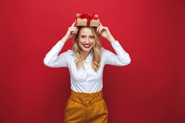 Mulher jovem e bonita loira em pé isolada sobre um fundo vermelho, segurando uma caixa de presente na cabeça
