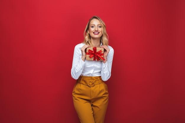 Mulher jovem e bonita loira em pé isolada sobre um fundo vermelho, segurando uma caixa de presente