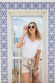 Mulher jovem e bonita loira em pé na parede coberta com azulejo de azulejos tradicionais portugueses.
