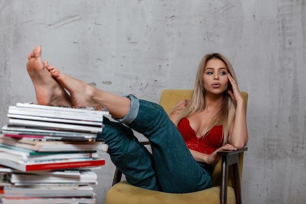 Mulher jovem e bonita loira em um elegante jeans azul em um luxuoso sutiã de renda vermelha, sentado em uma poltrona vintage macia em um quarto perto de uma pilha de livros e revistas.