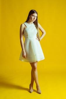 Mulher jovem e bonita loira em um lindo vestido de primavera, posando em um fundo amarelo no estúdio